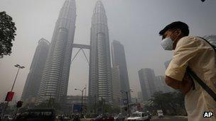 A pedestrian wearing a mask waits to cross a main road in front of Petronas Twin Tower covered by haze in Kuala Lumpur, Malaysia, 24 June 24 2013