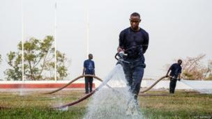 Fire fighters water the grass outside State House