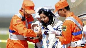 Chinese astronaut Wang Yaping, centre, goes out of the re-entry capsule of China's Shenzhou 10 spacecraft after its successful landing in Siziwang Banner, north China's Inner Mongolia Autonomous Region on 26 June 2013