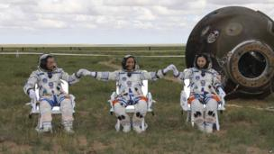 Astronauts Zhang Xiaoguang, Nie Haisheng and Wang Yaping (L to R) join hands after successfully landing back on Earth on 26 June 2013