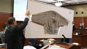 Assistant state attorneys John Guy (L) and Richard Mantei hold up Trayvon Martin's sweatshirt as evidence during George Zimmerman's trial in Seminole circuit court on Tuesday