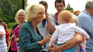 The Duchess of Cornwall stops to talk to a small child during the royal couple's visit