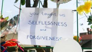 """A handwritten poster against railings outside the hospital reads: """"You taught us selflessness and forgiveness"""""""
