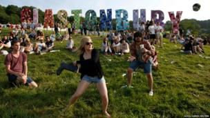 Festival goers play baseball, batting a beer can with a wellington boot, on the first day of Glastonbury music festival at Worthy Farm in Somerset