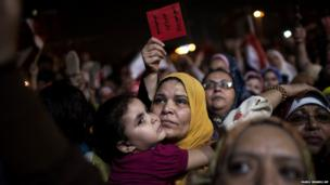 An Egyptian woman listens to a speech by President Mohammed Morsi during a demonstration at Tahrir Square in Cairo, Egypt