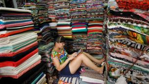 A fabric seller plays games on an iPad as she waits for customers at the Hom market in Hanoi