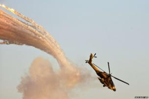 An Israeli Boeing AH-64 Apache longbow helicopter launches anti-missile flares