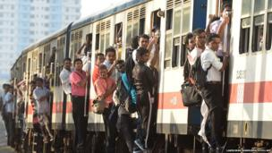 Sri Lankan commuters hold on to the sides of train coaches as they head to work in Colombo