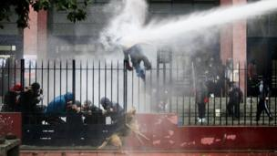A man jumps over a fence as police fire water canon