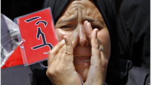 "An Egyptian protester shouts anti-Morsi slogans and holds a red card with Arabic reading ""leave"", during a protest in Tahrir Square (28 June 2013)."