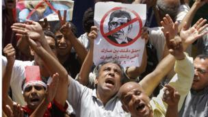 "Egyptian protesters shout anti-Muslim Brotherhood slogans as they hold posters depicting U.S. Ambassador to Egypt Anne Patterson and President Mohammed Morsi during a protest in Tahrir Square (28 June 2013). Arabic on the poster at centre reads, ""shave your beard show your shame, you will look like Mubarak."""