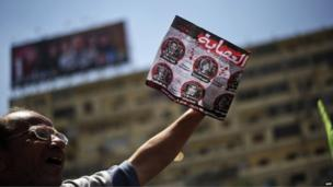An Egyptian protester holds a poster against television presenters and journalists as Islamists and Muslim Brotherhood supporters gather (28 June 2013).