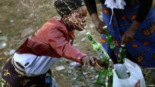 A member of the Indumiso Yamakholwa in Zion church smashing a green bottle, Johannesburg, South Africa - Friday 21 June 2013