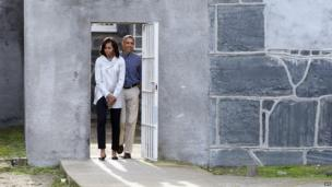 US President Barack Obama and First Lady Michelle Obama walk through a prison yard as they tour Robben Island.