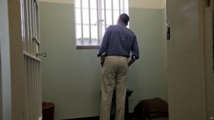 US President Back Obama peers out of a window in Section B, prison cell No. 5, on Robben Island, South Africa.