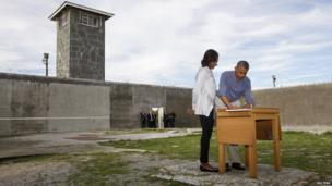 President Obama writes in a guest book as he tours Robben Island with First Lady Michelle