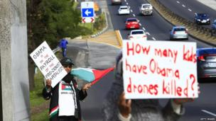 Protesters wave placards outside the University of Cape Town in advance of President Obama's speech there