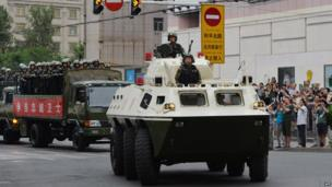 """Chinese paramilitary police ride in armoured vehicles and trucks during a """"show of force"""" ceremony in Urumqi after a series of terrorist attacks recently hit Xinjiang Province, on 29 June 2013"""