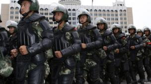 Armed paramilitary policemen run in formation during a gathering to mobilise security operations in Urumqi, Xinjiang Uighur Autonomous Region, 29 June 2013