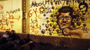 Egyptian opposition demonstrators sleep next to a wall covered in anti-Morsi graffiti outside the presidential palace in Cairo early on July 1, 2013