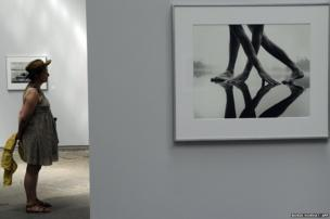 A visitor looks at pictures by Finnish photographer Arno Rafael Minkkinen