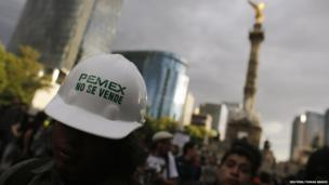"A demonstrator wears a helmet with a sticker that reads ""Pemex is not for sale"" during a protest against the privatisation of the state oil monopoly Pemex in Mexico City, 1 July"