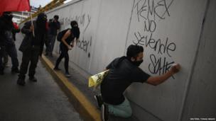 "A demonstrator writes graffiti, which reads ""Pemex is not for sale"", during a protest against the privatisation of the state oil monopoly Pemex in Mexico City, 1 July"