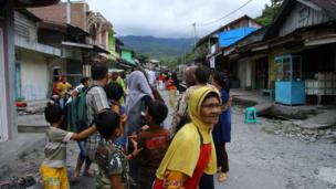Frightened Acehnese residents gather outside their homes after a quake shook Lampahan village in Aceh province, Indonesia, 2 July 2013