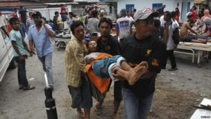 An injured resident is evacuated to the local clinic after a strong earthquake hit in Bener Meriah district in Central Aceh, Indonesia, 2 July 2013