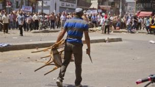 An Egyptian opposition protester holds a chair and knife during a clash between supporters and opponents of President Mohammed Morsi in downtown Damietta, Egypt
