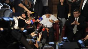 Evo Morales, center, talks to reporters at Vienna's Schwechat airport, Wednesday, July 3
