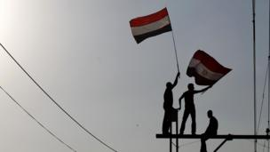 People wave the Egyptian national flag.