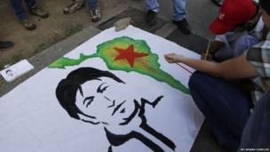 Venezuelans and Bolivians paint the face of Evo Morales on a banner outside Bolivia's embassy in a show of support for him in Caracas, Venezuela, Wednesday, July 3