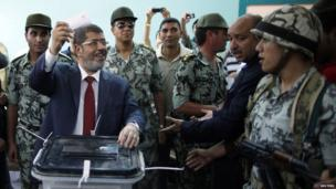 Soldiers shield Mohammed Morsi as he votes in al-Sharqia, 16 June 2012