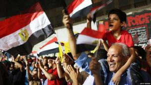 A man carries a little boy on his shoulders while waving the Egyptian flag during celebrations following the army action to depose President Mohammed Morsi