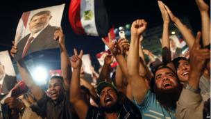 Muslim Brotherhood members and supporters Mohammed Morsi shout religious and political slogans while holding his portrait during a rally outside Cairo's Rabaa al Adaawyia mosque