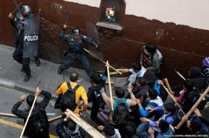 Students clash with riot police during a demonstration against the government in Lima