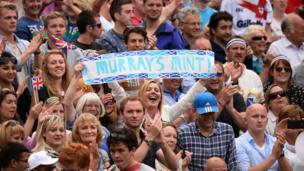 Woman holds Murray's Mint banner.