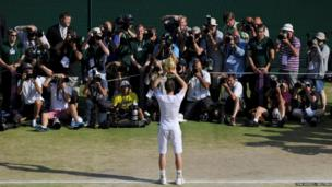 Andy Murray of Britain holds the winners trophy at the Wimbledon Tennis Championships in London