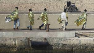 Migrants walk along dock in Lampedusa