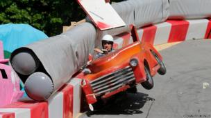 A competitor crashes his home made vehicle during the Red Bull Soapbox Race