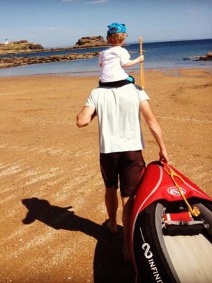 Man and boy pull a canoe