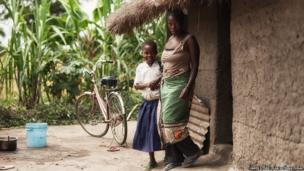 Sylvia and her mother outside their family home in rural Tanzania