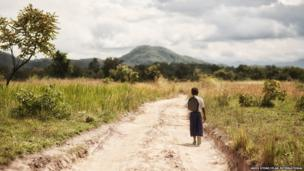 Tanzanian schoolgirl Sylvia on a path off a main road