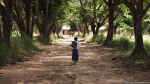 Tanzanian schoolgirl Sylvia walking down a tree-lined avenue to her school