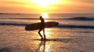 A surfer returns from the evening waves at Ballyliffen Beach, in County Donegal - photographed by Niall McCaughan