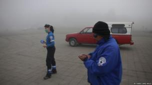 Rescue workers stand in the Paso de Cortez crossing as volcanic ash and rain fall on 6 July