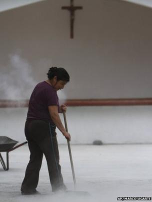 A resident sweeps volcano ash from the Popocatepetl volcano outside a church in San Pedro Nexapa, Mexico, 8 July