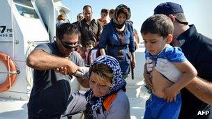 Coastguards help migrants disembark off boat in Ierapetra, Crete, on 9 July 2013