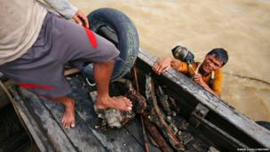 A diver holds his mask as he attempts to get up on a small boat on Yangon river